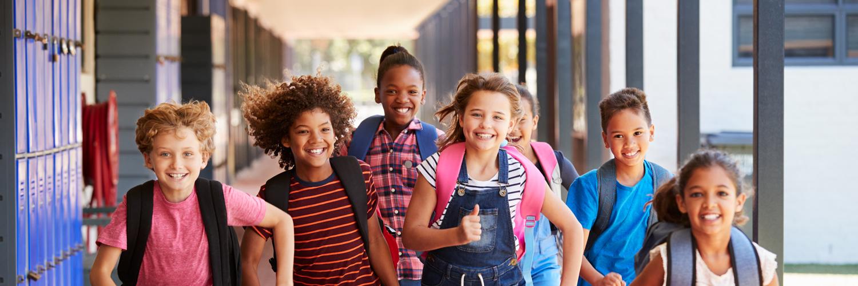 Barn i en skola springer och är glada
