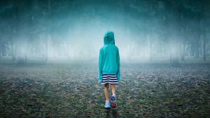 bild på en flicka som står i ett öde landskap med ryggen mot kameran.