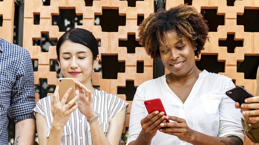 två personer står med sina telefoner mot en vägg