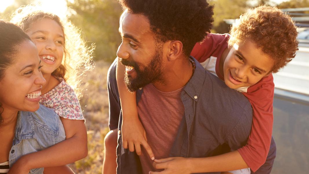 en familj bestående av mamma och pappa. två barn rider på vardera förälders rygg