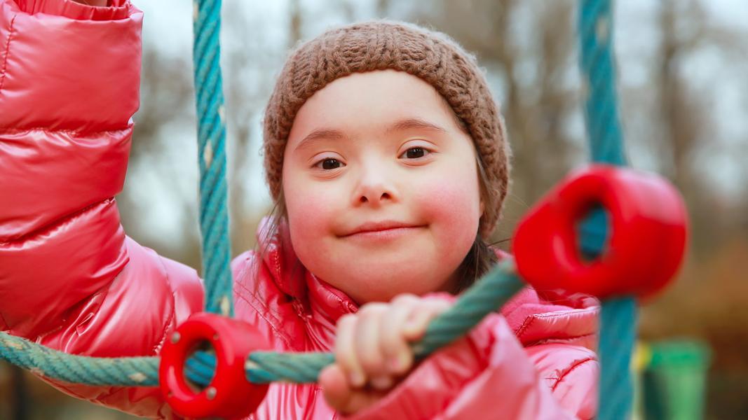 flicka med rosa jacka i en klätterställning