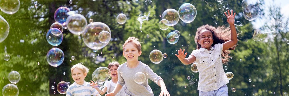 Fyra barn springer utomhus med såpbubblor runt dem. De är glada och skrattar