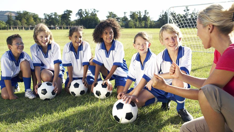 en idrottsledare sitter på en gräsplan med barn som tränar fotboll.