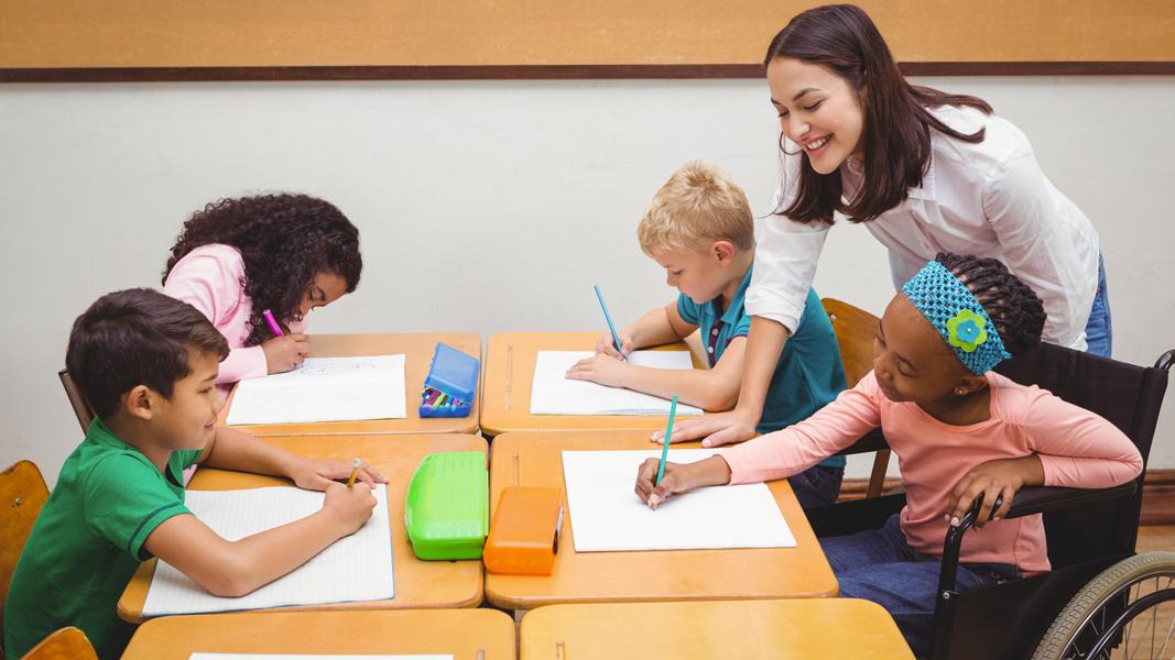 en lärare hjälper sina elever vid ett bord i klassrummet.