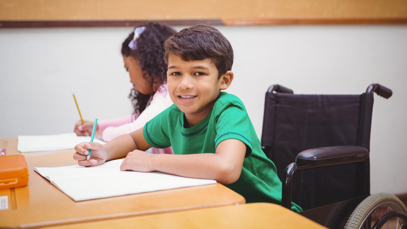 en pojke i rullstol i ett klassrum ler mot kameran.