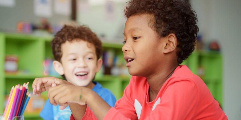 två kompisar sitter i ett klassrum
