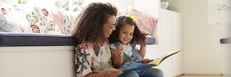 Mamma sitter på golvet med sin dotter och läser en bok