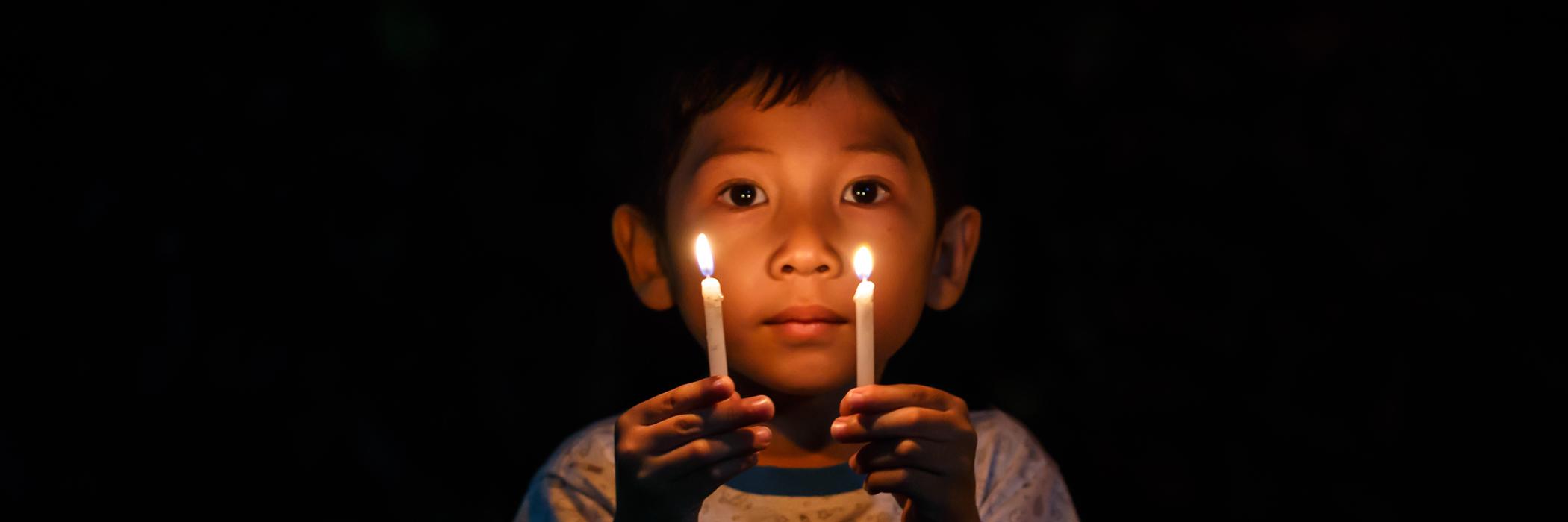 Pojke håller i två ljus mot en mörk bakgrund