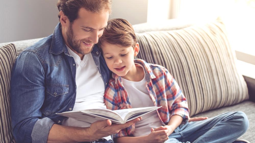 pappa sitter med sin son i soffan och läser en bok