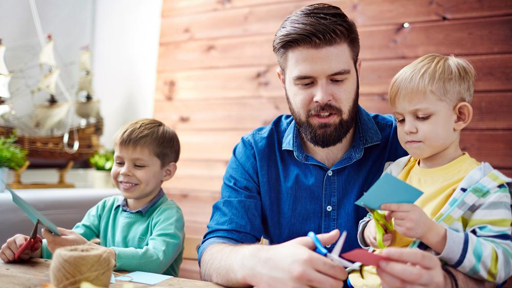 pedagog i förskolan sitter med två barn vid ett bord och klipper i papper