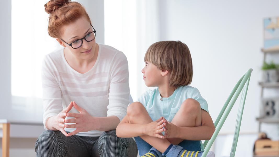 en vuxen kvinna och en pojke pratar med varandra