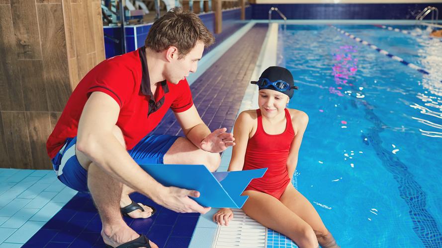 tjej som simmar pratar med sin tränare.