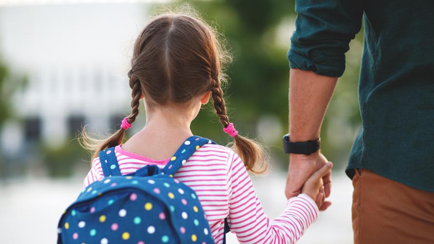 en flicka med skolväska som håller sin pappa i handen på väg till skolan.