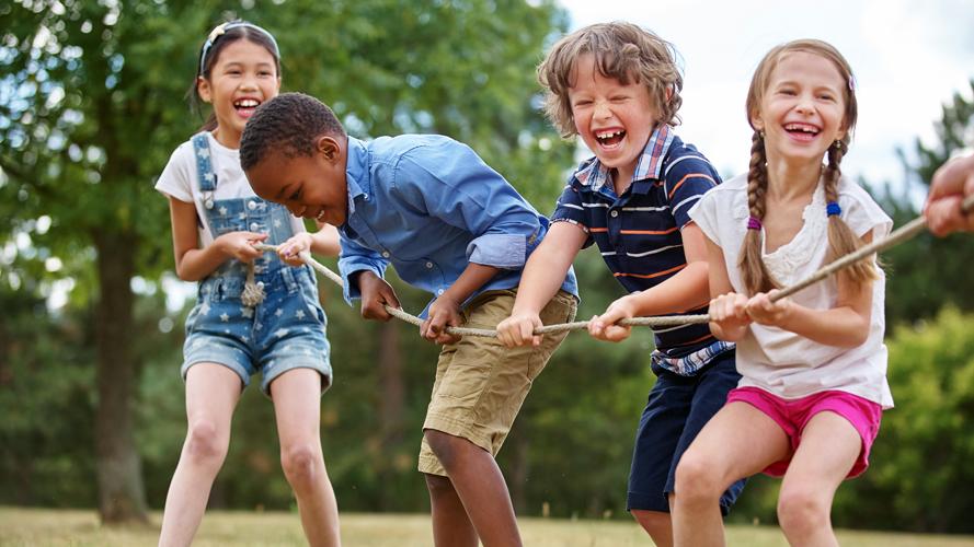 Glada skolbarn leker med ett rep tillsammans