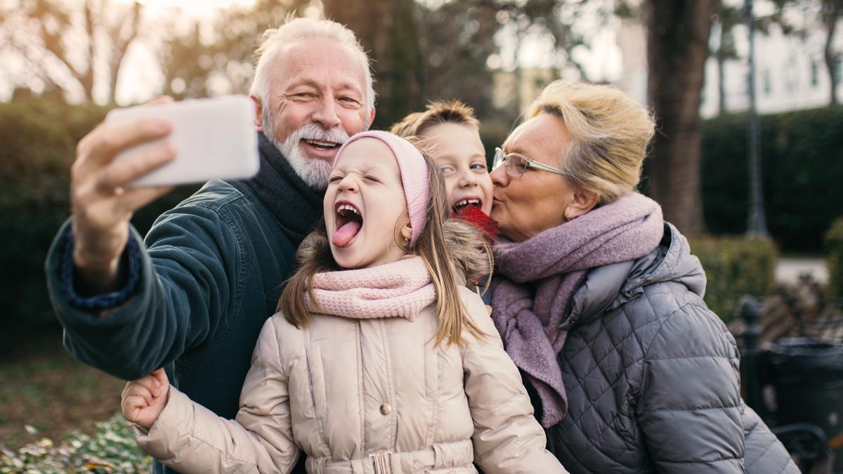 mormor och morfar tar en selfie med två barnbarn