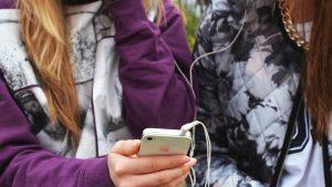 två kompisar håller i en smartphone. de är anonyma och man ser inte deras ansikten.