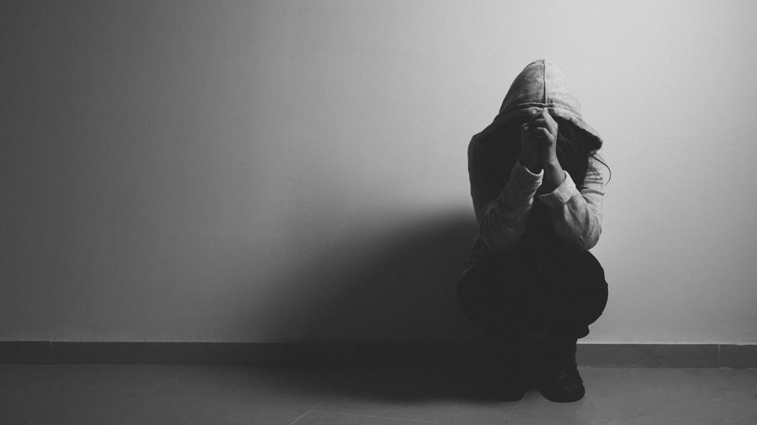 svartvit bild på en tjej som sitter på huk mot en vägg