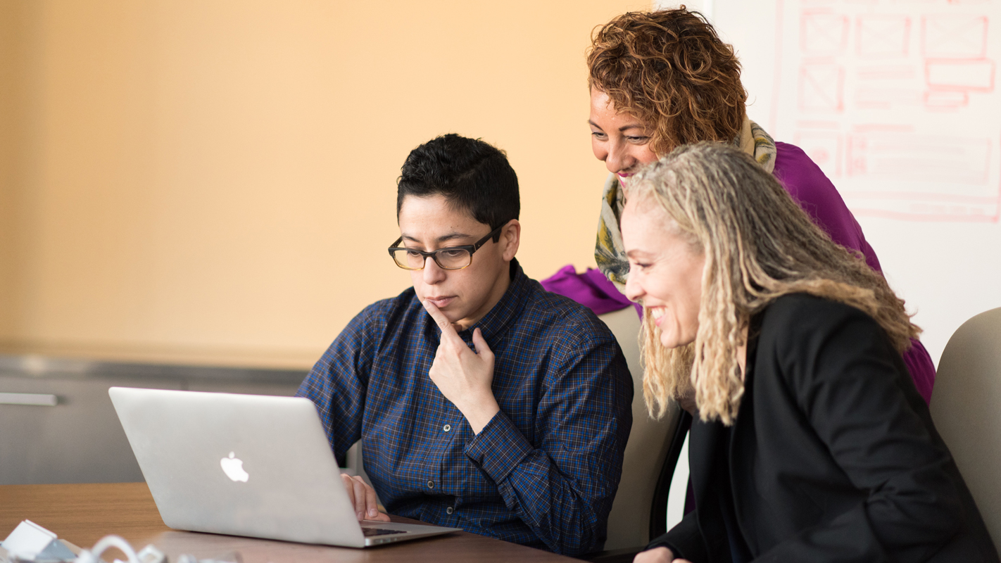 tre lärare tittar på en dator.
