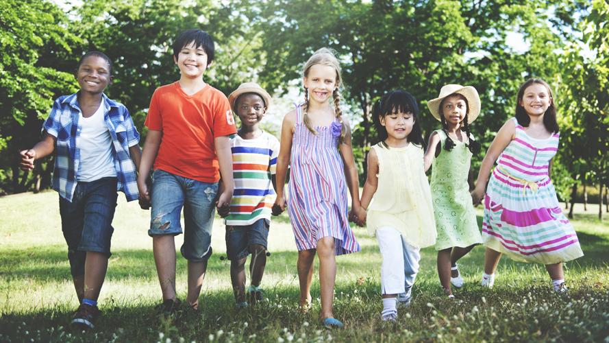 lada barn går på en gräsmatta. de håller varandra i händerna och ser glada ut.