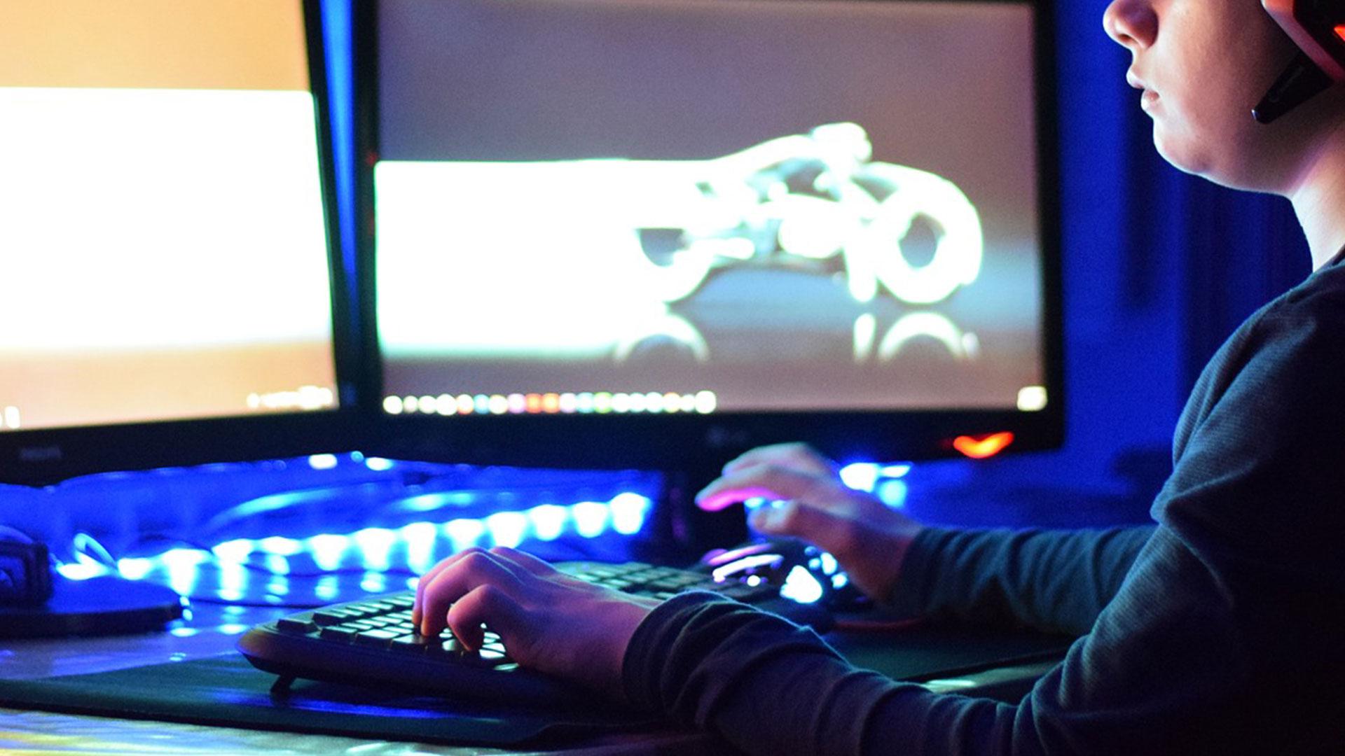 en pojke sitter vid en dator och spelar