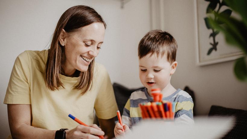 en mamma sitter tillsammans med sin son vid ett bord och ritar.
