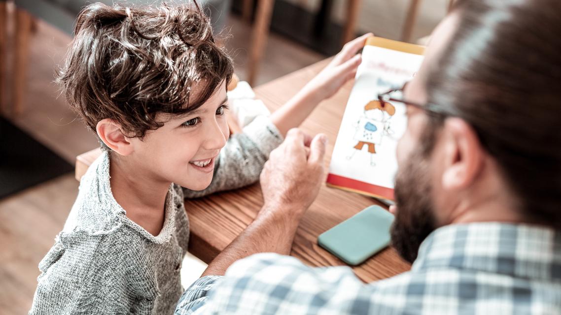 en pojke och hans pappa sitter vid ett bord och tittar i en bok