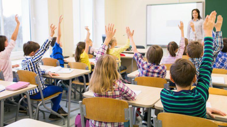 barn sitter vid sina bänkar i ett klassrum och räcker upp handen.