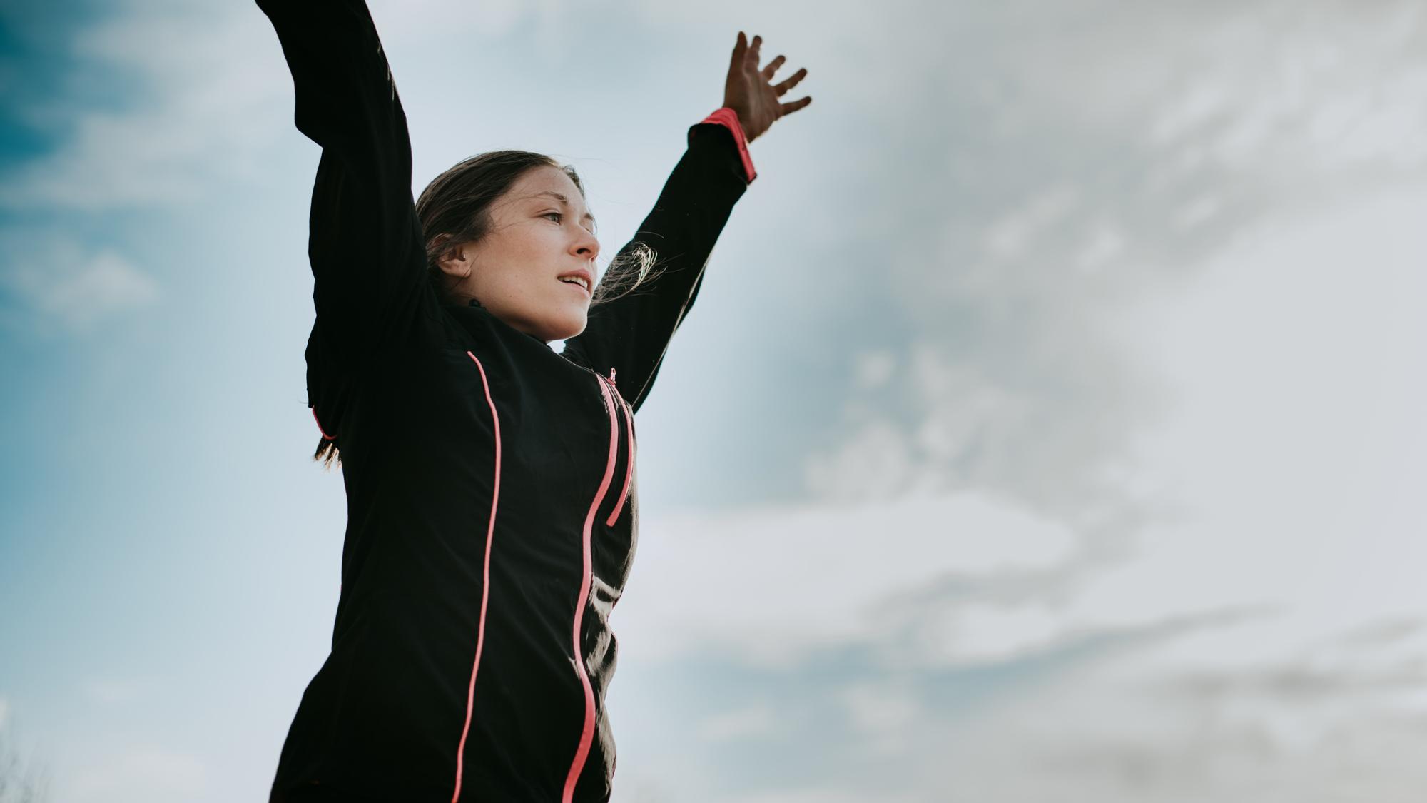 kvinna har på sig träningskläder och lyfter armarna mot himlen.