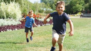Två barn springer på en gräsmatta.