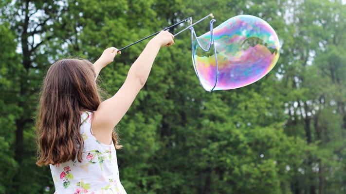 en flicka gör en stor såpbubbla.