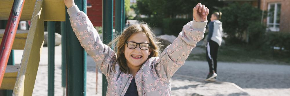en flicka på en lekplats serglad ut och sträcker upp armarna i luften.