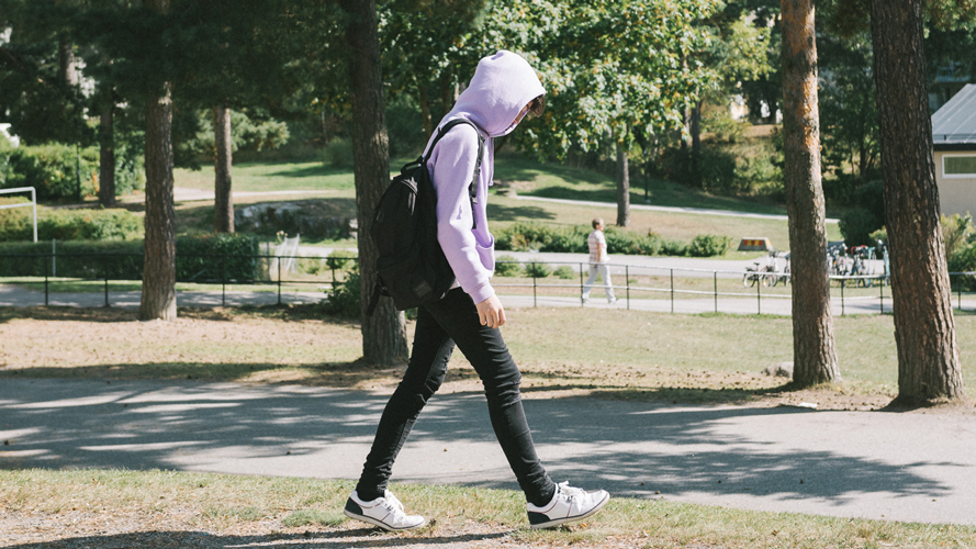 Kille på väg till skolan med ryggsäck. han har luvtröja som döljer hans ansikte.