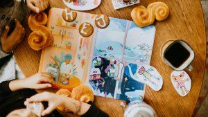 snällkalendern 2019 ligger på ett bord omringad av pepparkakor, lussebullar och kaffe