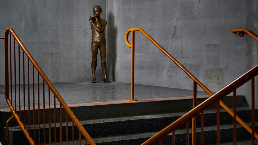 bronsskulptur föreställande ett barn i ett utsatt ögonblick