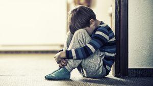 en pojke sitter ihopkrupen på ett golv i skolmiljö