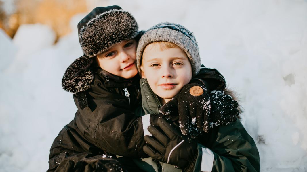 två barn leker i snön på vintern