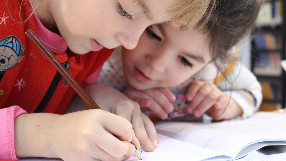 barn som lutar sig över ett papper och skriver eller riterAC