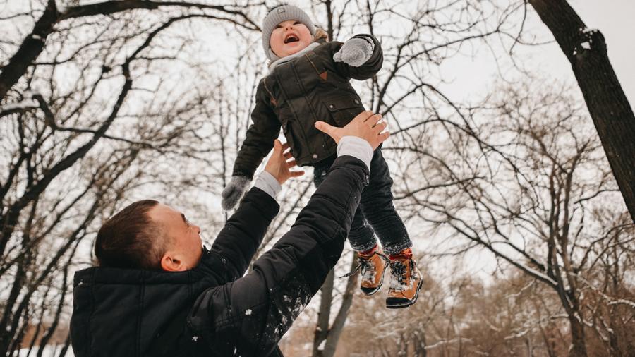 pappa leker med sitt barn på vintern