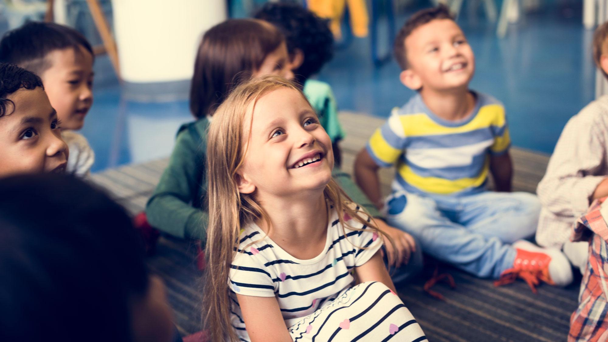en samling skolbarn sitter på golvet. de lyssnar på sin lärare