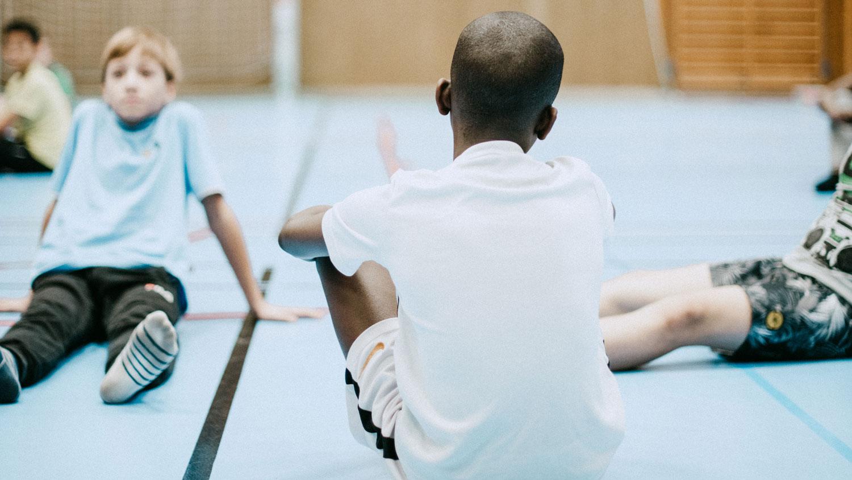 bild på fyra barn som sitter på golvet i en idrottssal