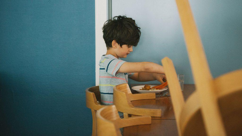en pojke sitter själv i skolans matsal
