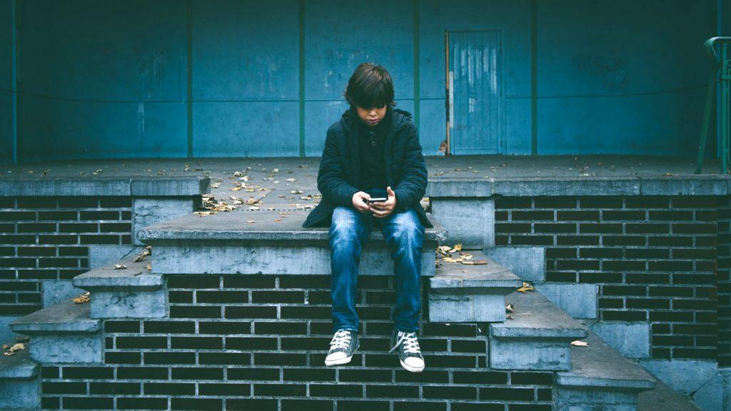 barn sitter själv och spelar på en telefon.