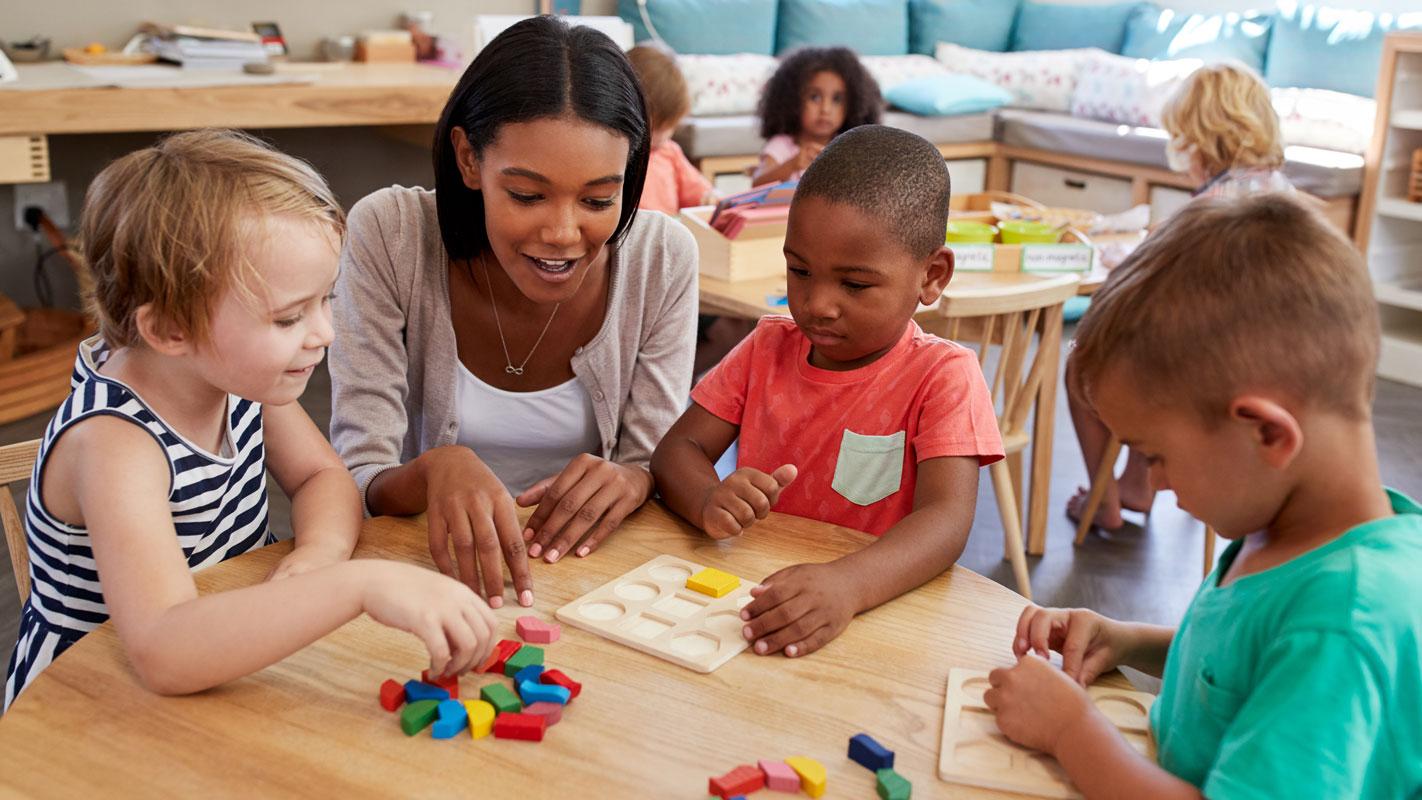 lärare i förskolan sitter med tre barn vid ett bord