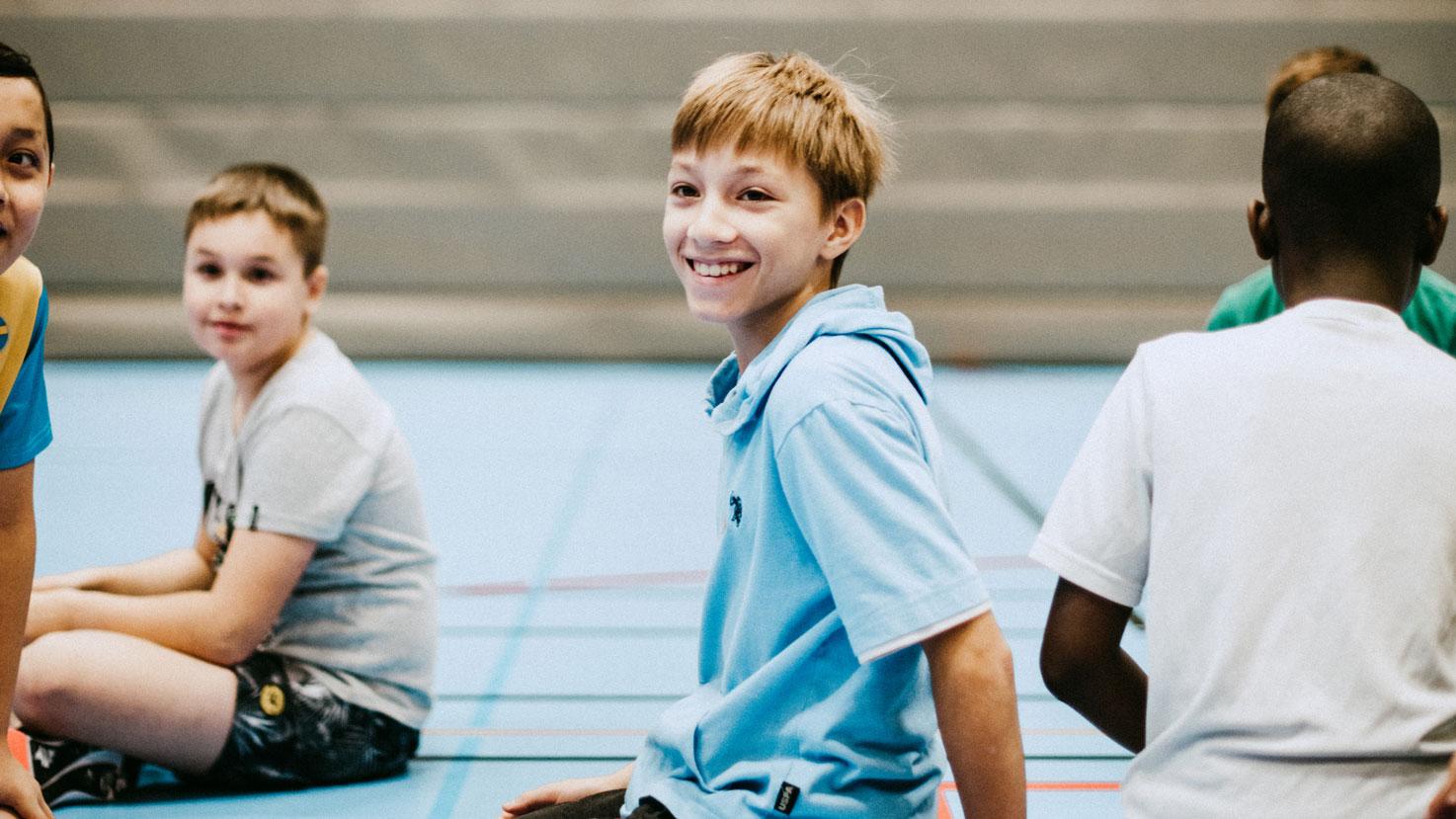 flera barn sitter på golvet i en idrottssal