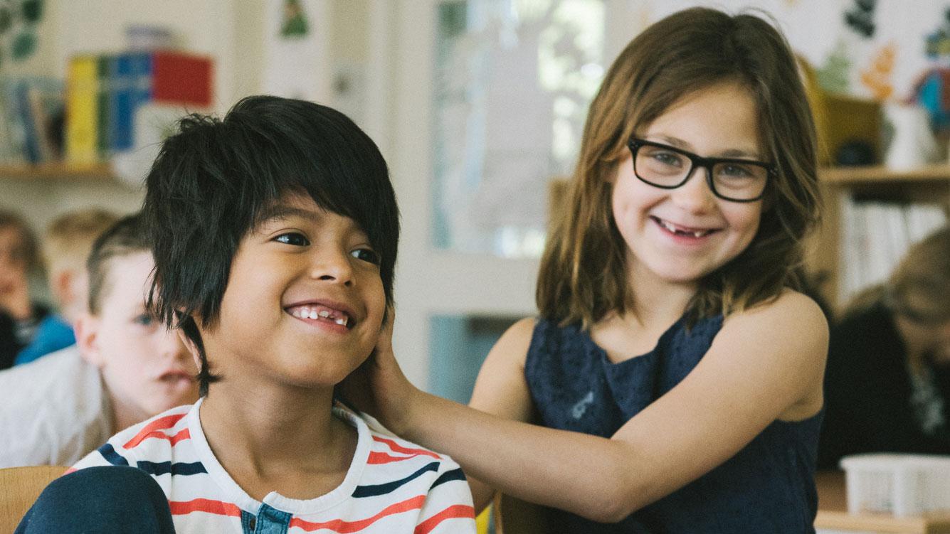 två klasskompisar leker i ett klassrum