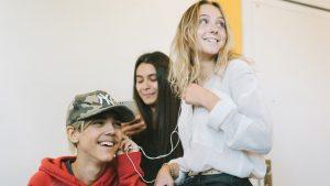 tre tonåringar lyssnar på musik från en mobiltelefon.
