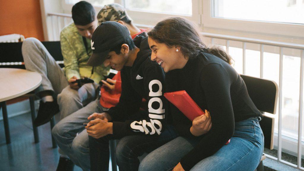 några kompisar skrattar och tittar på en mobiltelefon
