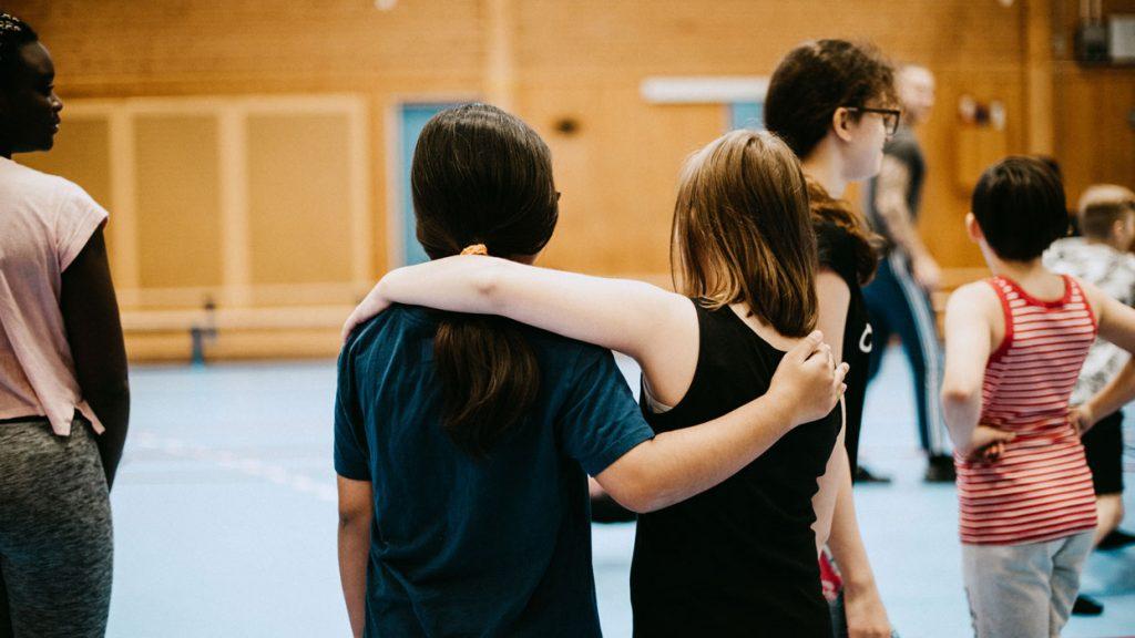 två vänner håller om varandra i skolans idrottsal.
