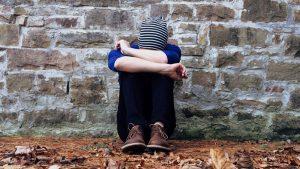 ett barn sitter ensam på marken