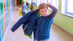 pojke som sätter på sig jackan i en skolkorridor.
